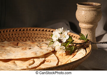 Chalice with red wine and pita bread in a basket