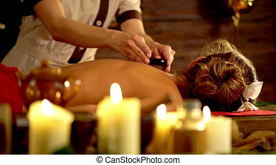 Lastone therapy massage in spa salon. In foreground are burning candles. 4k