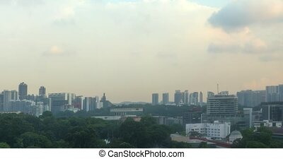 Clouds drift and billow across a darkening sky in timelapse, over a modern and green cityscape of Singapore. 4k DCI footage