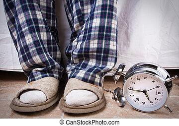 Late again - Alarm clock in the floor near an recently awake...