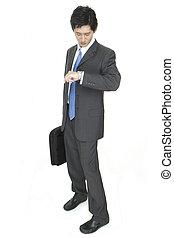 Late - An asian businessman checks his watch