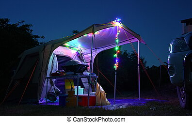 Late Evening on a Camp Site. Illuminated tent at twilight. Camping with tent light and with camping equipment.