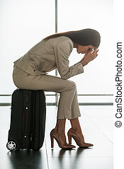 Late for flight. Depressed young businesswoman in formalwear holding head in hands while sitting on her suitcase in airport