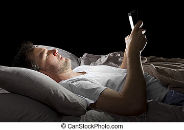 Late Night Browsing - male in bed browsing the internet late...