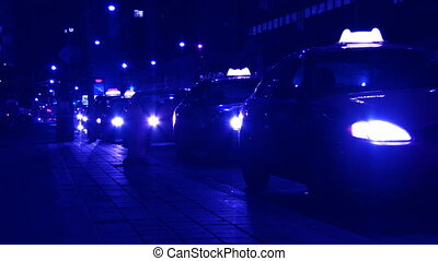 Night-shot of cabs waiting at downtown taxi-stand. Colour graded with a blue tint. Toronto, Ontario, Canada.