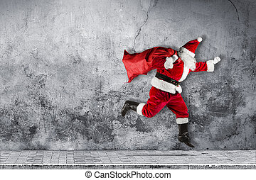 late Santa claus in a hurry with traditional red white costume and bag full of presents running jumping abstract funny christmas xmas concrete background