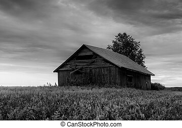 The summer sun sets behind an old abandoned barn house in the Northern Finland.