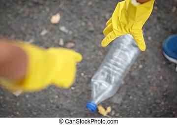 latex, ökologie, asphalt, hintergrund., concept., auf, gelber , plastik, kinder, schutz, handschuhe, flasche, hände, pflückend