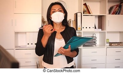 Latin american female business assistant wearing medical face mask standing in office with clipboard, noting tasks. Concept of social distance in coronavirus pandemic