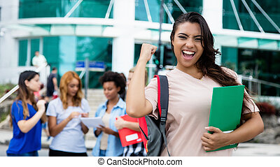 Latin american female student celebrating successful exam...