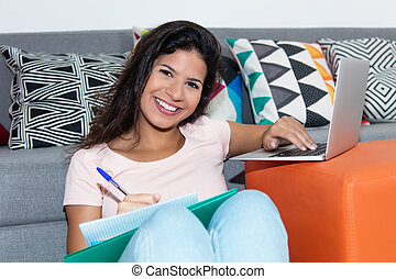 Latin american female student working with laptop at home