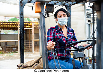 woman in protective face mask working on forklift