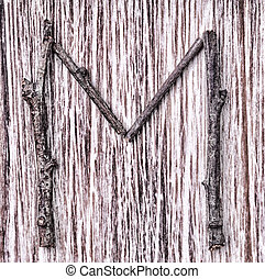 Latin capital alphabet letter M made from sticks on vintage surface
