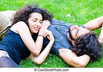 Latin Couple on meadow sleeping in summer