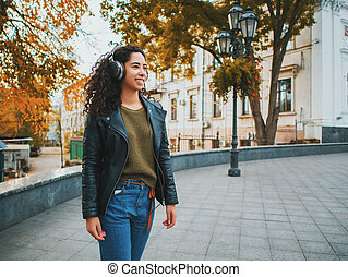 Latin curly haired girl listening music in headphones in autumn park. Beautiful young hispanic lady smiling, singing and enjoying melody outdoor.