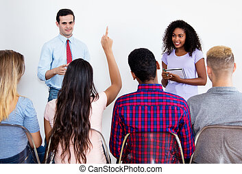 Latin female student asking questions of other students
