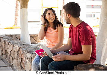 Beautiful Latin college student flirting and talking to a guy she likes at school