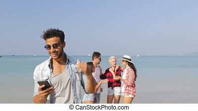 Latin Man Answer Phone Call With People Group On Beach Have...