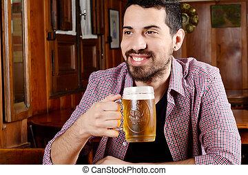 Latin man drinking beer at a bar.
