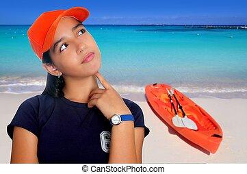 Latin teen hispanic pensive girl orange cap in Caribbean beach kayak