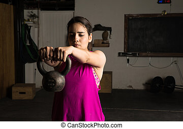 Latin woman lifting a kettlebell