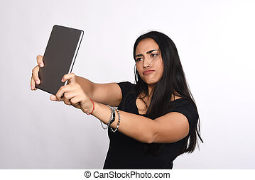 Latin woman taking selfie with tablet