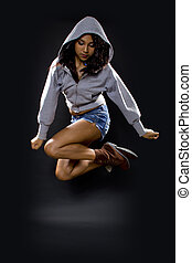 latina dancer wearing a hoodie jumping. shot on a black background.