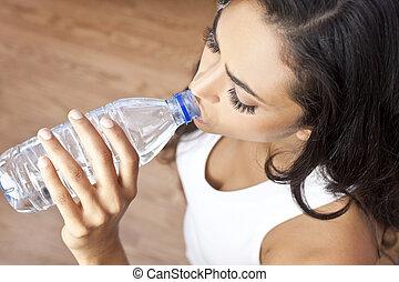 Beautiful Latina Hispanic young woman or girl drinking water bottle at gym