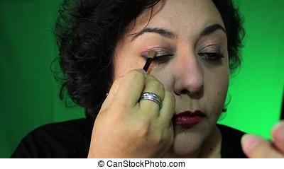 latina in 40's applies eye makeup - latina applies her eye...