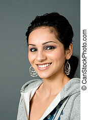a young latina smiles with large earrings and casual sweater