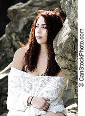 Latina Woman Sitting On Rocks In Bikini With White Knit Cover