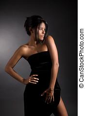 latino beauty - Beautiful latino girl standing on black...