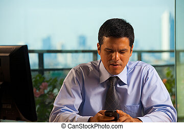 A hispanic businessman receives bad news by text (sms) on his smartphone. 30s latino American male of mixed Brazilian - Mexican descent.