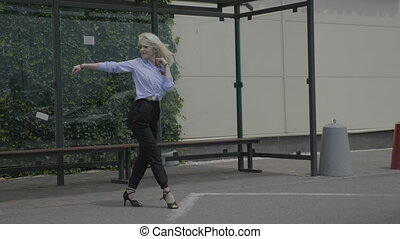 Latino dance of blonde employee showing artistic skills elegant moves and dancing talent in public while she waiting the bus