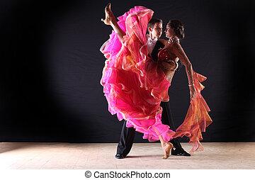 Latino dancers in ballroom against black background