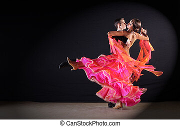 Latino dancers in ballroom against black background