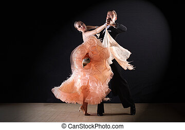 Latino dancers in ballroom against on black