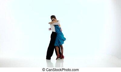 Latino dancing couple of professional elegant dancers,slow motion. White studio