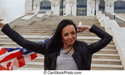 Latino girl with wavinf US flag in hands behind her back...