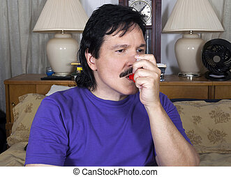 Latino man uses his asthma inhaler in his bedroom