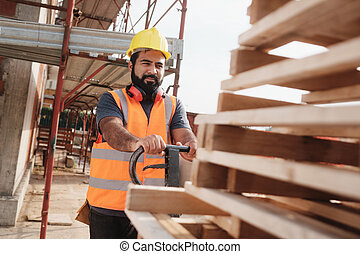 Latino Manual Worker With Forkift Pallet Stacker In Construction Site