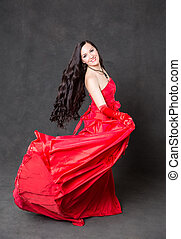 Latino Woman with long hair in red waving dress dancing in...