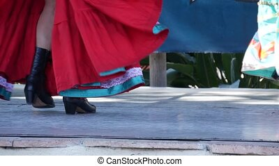 Latino women in colourful traditional dresses dancing Jarabe...