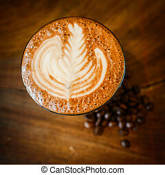 Latte art, coffee and coffee beans on wooden background