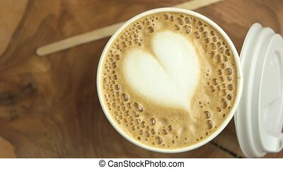 Latte art heart. Coffee cup and lid.