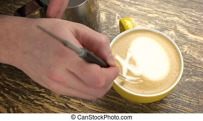 Latte art pen. Barista decorating coffee.