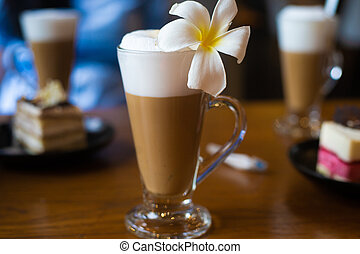 Latte in a glass mug stands on a wooden table with a plumeria flower