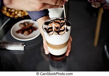 Latte macchiato coffee with chocolate decoration and straw