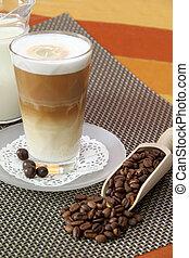 Latte Macchiato in glass with coffee grain on brown background