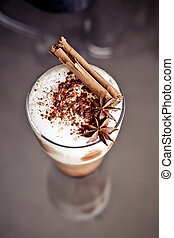 Latte macchiato with cinnamon and anise stars on the table